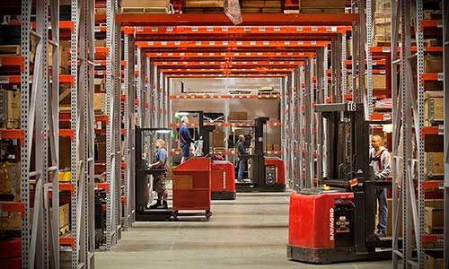 Four warehouse workers use Raymond brand lift trucks to complete tasks