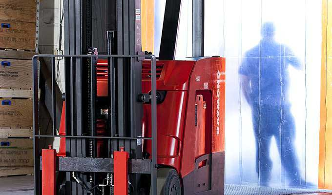 Close-up of reach truck in warehouse with worker standing nearby