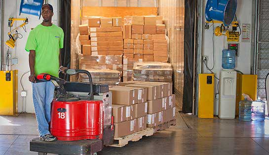 Worker uses rental pallet jack for material handling in warehouse setting