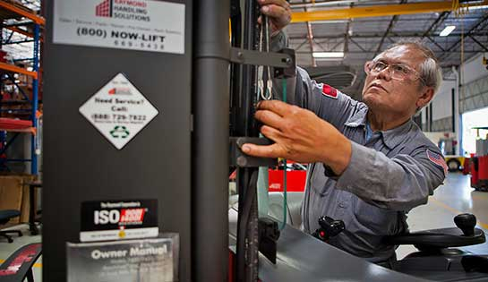 Forklift technician performs quality inspection on lift truck
