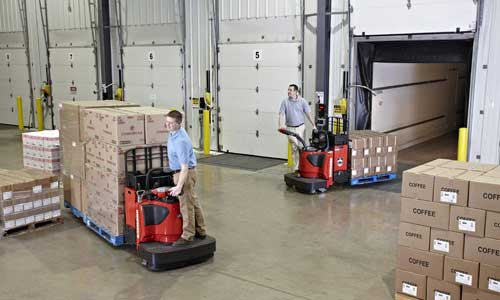 Two warehouse employees transport goods with used lift trucks