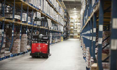 Automated Raymond courier forklift navigates down a warehouse aisle