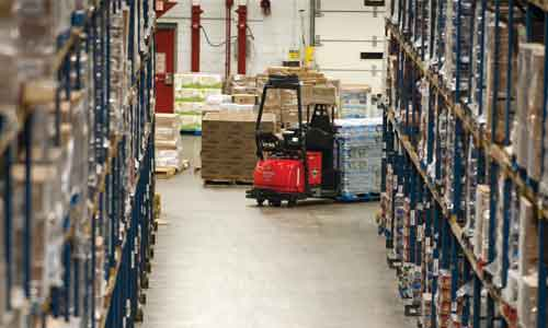 Automated Raymond courier lift truck transports pallets through warehouse aisle