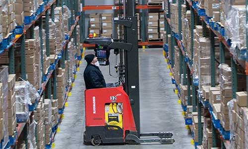 Operator in warehouse without automation uses forklift to reach product on shelves