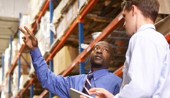 Warehouse managers discuss data insights from integrated reach truck technology to improve productivity