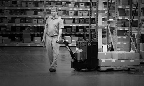 Warehouse worker hauls product using the LRW35 pallet jack
