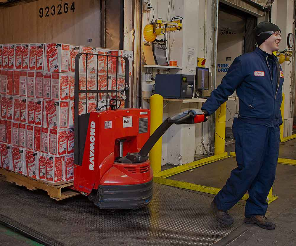 Laborer in warehouse uses Raymond pallet truck to unload pallet of product from receiving dock