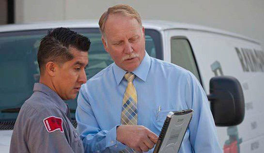 Forklift technician and manager discuss reports generated from labor management system using tablet device