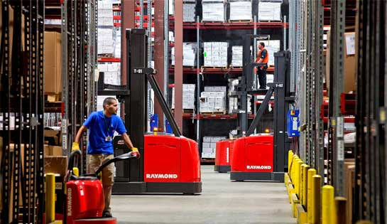 Two workers use rental lift trucks from Pengate in the warehouse